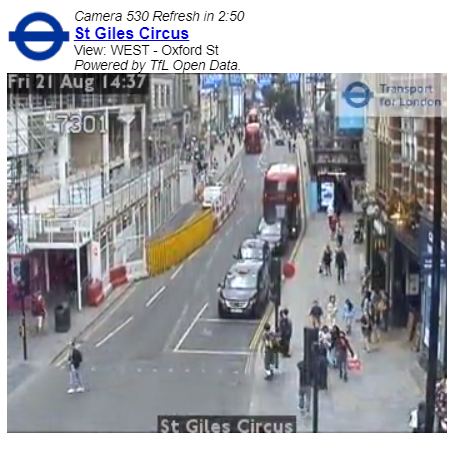 Segment of traffic camera video footage from St Giles Circus in London. Cars, pedestrians and buses are clearly visible in the image.